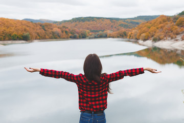 Young woman wearing red plaid shirt standing alone near the lake in autumn. Weekend outdoors, cloudy cold weather, fall colors. Enjoying freedom and nature. Back view. Arms up.