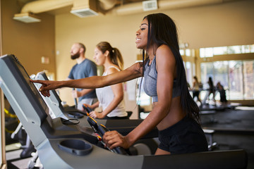 african american woman using treadmill in gym with other people