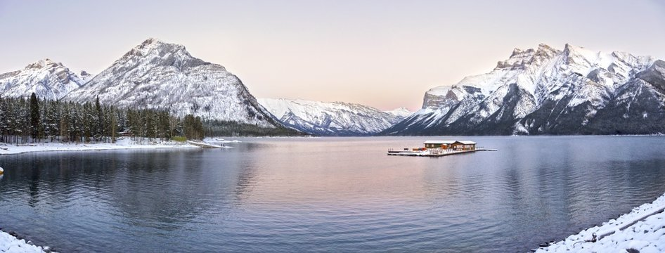 Wide Panoramic Sunset Landscape and Distant Snowcapped Rocky Mountains at Lake Minnewanka in Banff National Park, Alberta, Canada