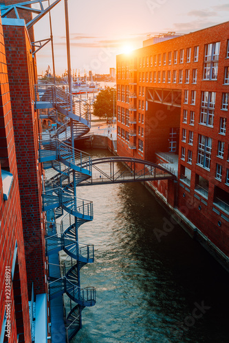 Circular Staircase Bridge Over Canal And Red Brick Buildings In The