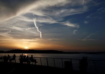 People sit along the promenade to watch the sunset in Qawra