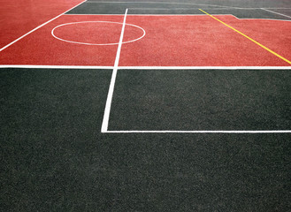 Surface of red and black sports field with white lines. Playing ground for games