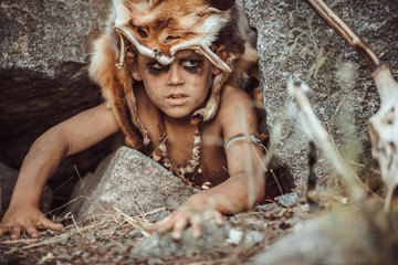 Caveman, manly boy hunting outdoors. Prehistoric tribal boy outdoors on nature. Young shaggy and dirty savage, warrior and hunter hiding in an ambush behind a stone in cave. Primitive ice age man in