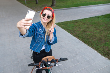 Smiling stylish woman standing with a bicycle in the park, posing on the smartphone camera. Fashion girl make selfie with the bike in the park.
