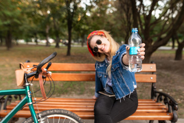 Happy, stylish girl sitting on a bench in a park near a bicycle and shows a bottle of water in the camera. A bottle of water in the hands of a girl close-up. Focus on the bottle