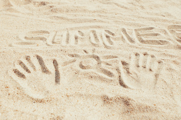 Word summer and hand prints on sand.