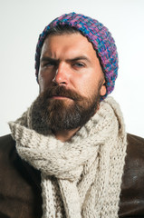 Autumn-winter fashion. Handsome bearded man in knitted hat, scarf&leather jacket. Fashion, beauty, clothing, style concept. Man in fashionable cap, scarf, coat. Autumn-winter clothes. Demi-season wear