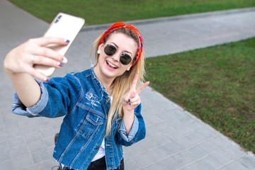 Stylish happy girl in sunglasses, a denim jacket and a scarf standing in the park, takes selfie on smartphone and smiling.Smiling woman posing for the camera smartphone outdoors in the park.
