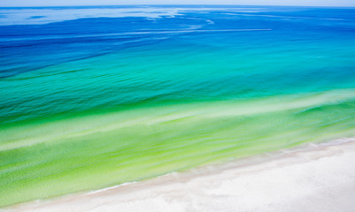 Blue Ocean and Coastline / Abstract landscape of deep blue and turquoise green ocean water along a white sand beach.