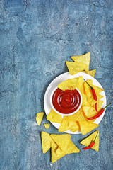 Top view on mexican nachos chips with spicy red sauce or dip in white bowl and hot chilli pepper