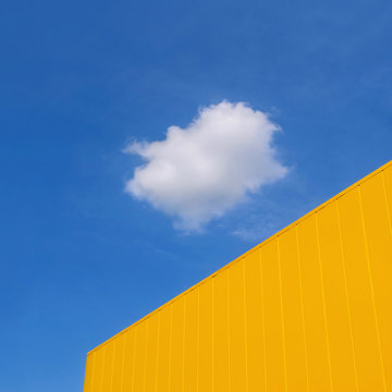 New yellow metal panel construction, wall of building with blue sky and white cloud in background