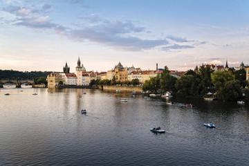 Vltava river against sky in city during sunset