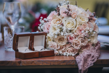 Close-up of bouquet with wedding rings on wooden table