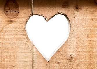 Heart carved in dark wooden wall texture, with bokeh background isolated