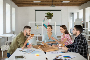 Group of young creative people eating pizza together pending time at work in modern office