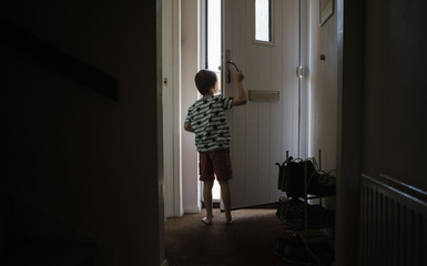 Rear view of boy looking through doorway while standing at home