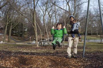 Father carrying daughter while looking at happy son playing on swing in park during winter