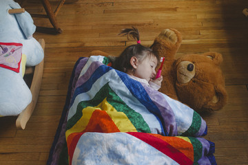 High angle view of girl holding toothbrush while sleeping on teddy bear at home