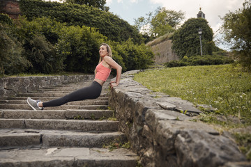 Low angle view of woman smiling while exercising on steps at park