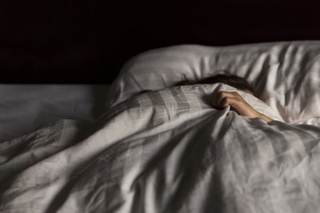 Sick girl with blanket sleeping on bed at home