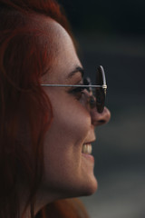 Close-up of happy woman wearing sunglasses outdoors