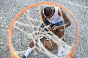 High angle view of sportsman with basketball using smart phone while sitting at court