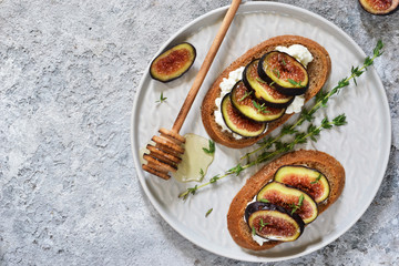 Toasts with ricotta, figs and honey for breakfast on a concrete background. Gourmet breakfast.
