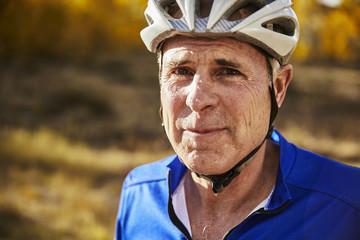 Close-up portrait of tired sweaty senior man wearing bicycle helmet on field