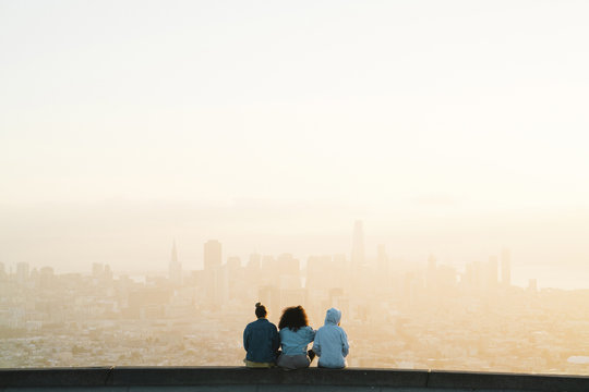 Rear view of female friends looking at cityscape while sitting against clear sky during sunset