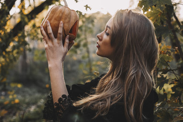 Side view of young woman holding jack o lantern in forest
