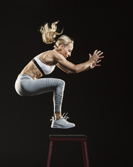 Full length of woman jumping on stool against black background
