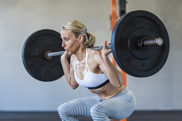 Confident woman lifting barbell while exercising in gym