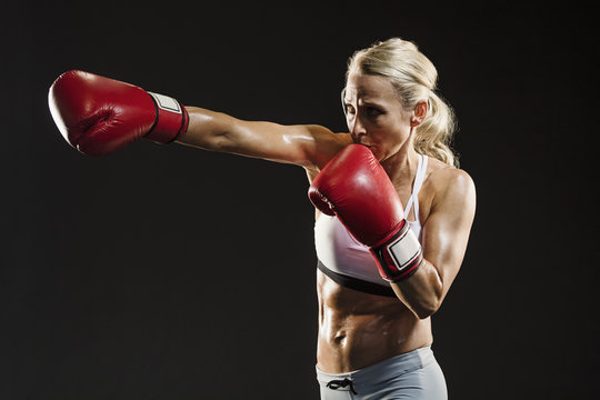 Determined sweaty woman practicing kickboxing against black background