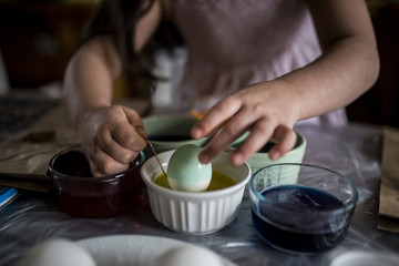 Midsection of girl coloring Easter eggs on table at home