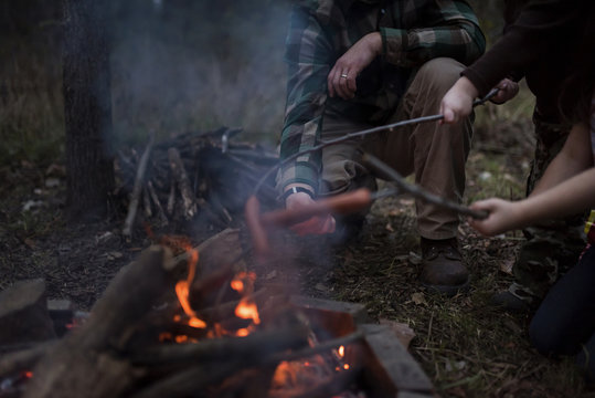 Family roasting sausages on stick over campfire in forest