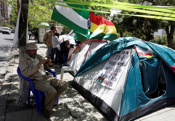 Opposition activist sits next to a tent during a hunger strike in protest against President Evo Morales' bid for re-election in 2019, in La Paz