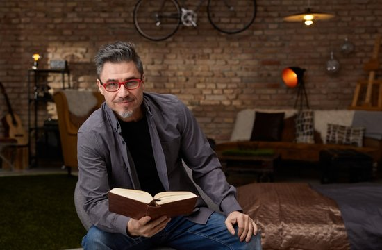 Older white man reading book at home