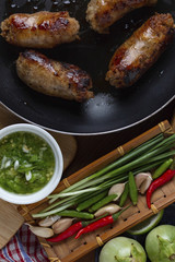 Close-up of cooked sausages in cooking pan with ingredients on table