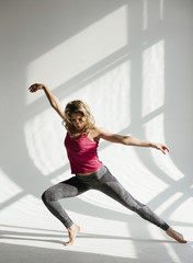 Woman with arms outstretched dancing against white wall in studio