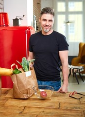Happy older man in kitchen with shopping bag