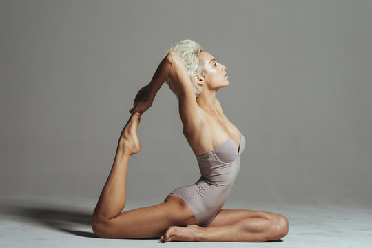 Woman practicing one-legged king pigeon pose against gray background