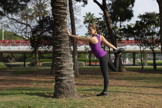 Woman stretching leg while leaning on tree trunk in park