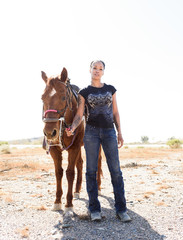 Portrait of woman standing by brown horse on dirt road against clear sky during sunny day