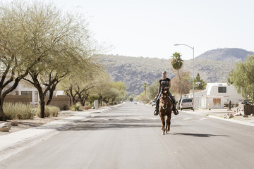 Woman horseback riding on road against clear sky during sunny day