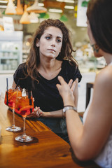 Female friends with aperitifs on table talking while sitting in restaurant