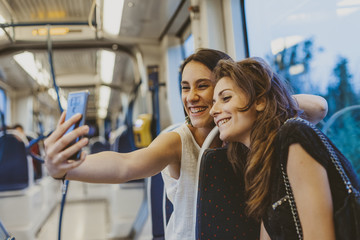 Happy female friends taking selfie with smart phone while traveling in tram