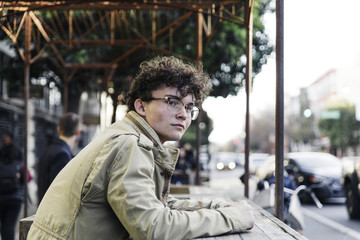 Thoughtful man wearing jacket while sitting at sidewalk cafe