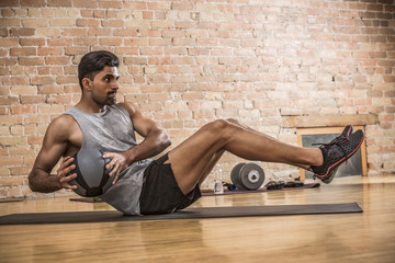 Confident male athlete exercising with medicine ball while sitting on exercise mat against brick wall in gym