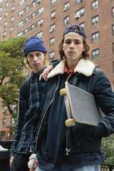 Low angle portrait of confident male friends with skateboard standing against building in city