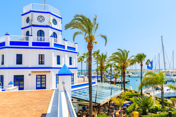 Beautiful lighthouse building and palm trees in Estepona port on Costa del Sol coast, Spain